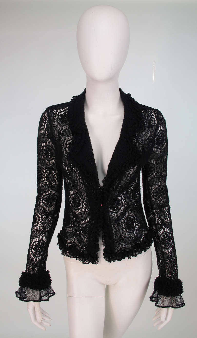 Chanel black lacy wool sweater from 04A collection...Long sleeve has no closures,  Notched collar, V front neckline...Sweater us ruffle trimmed at facings, neckline and cuffs, cuffs have an additional black lace flounce...In barely worn