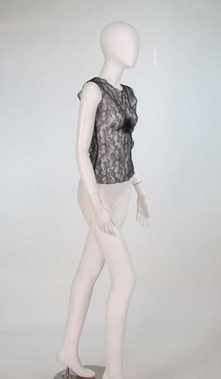 Chanel black lace sleeveless top from 2004A collection...Pull on top is unlined...Lace trimmed neckline and arm openings...Lace is gathered at the center front to form an abstract flower...Fits like a modern 2-4...