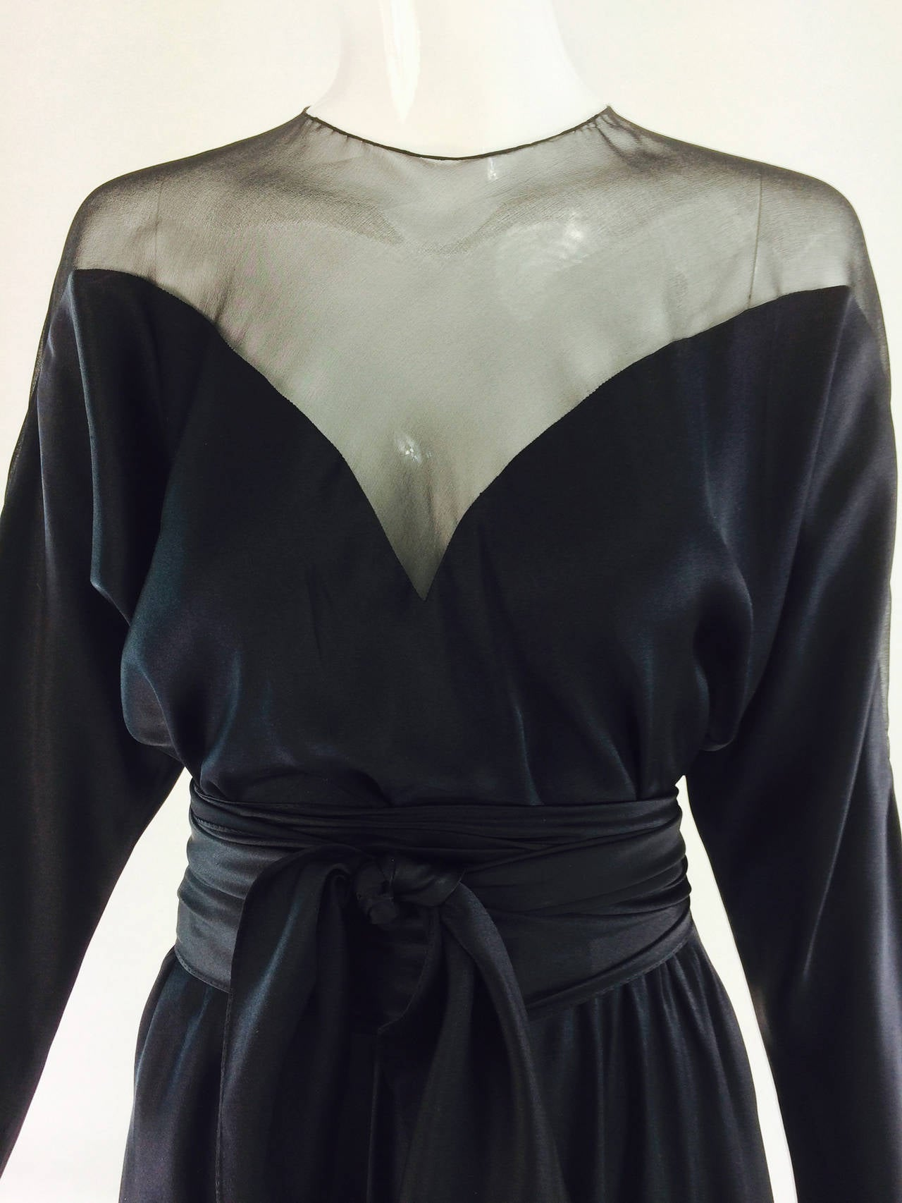 1970s Halston black silk chiffon silk charmeuse bias cut cocktail dress. A similar dress was worn by Liza Minnelli in Halston's 1971 made to order show. Cocktail dress with dolman sleeves, the upper bodice is done in sheer black silk chiffon