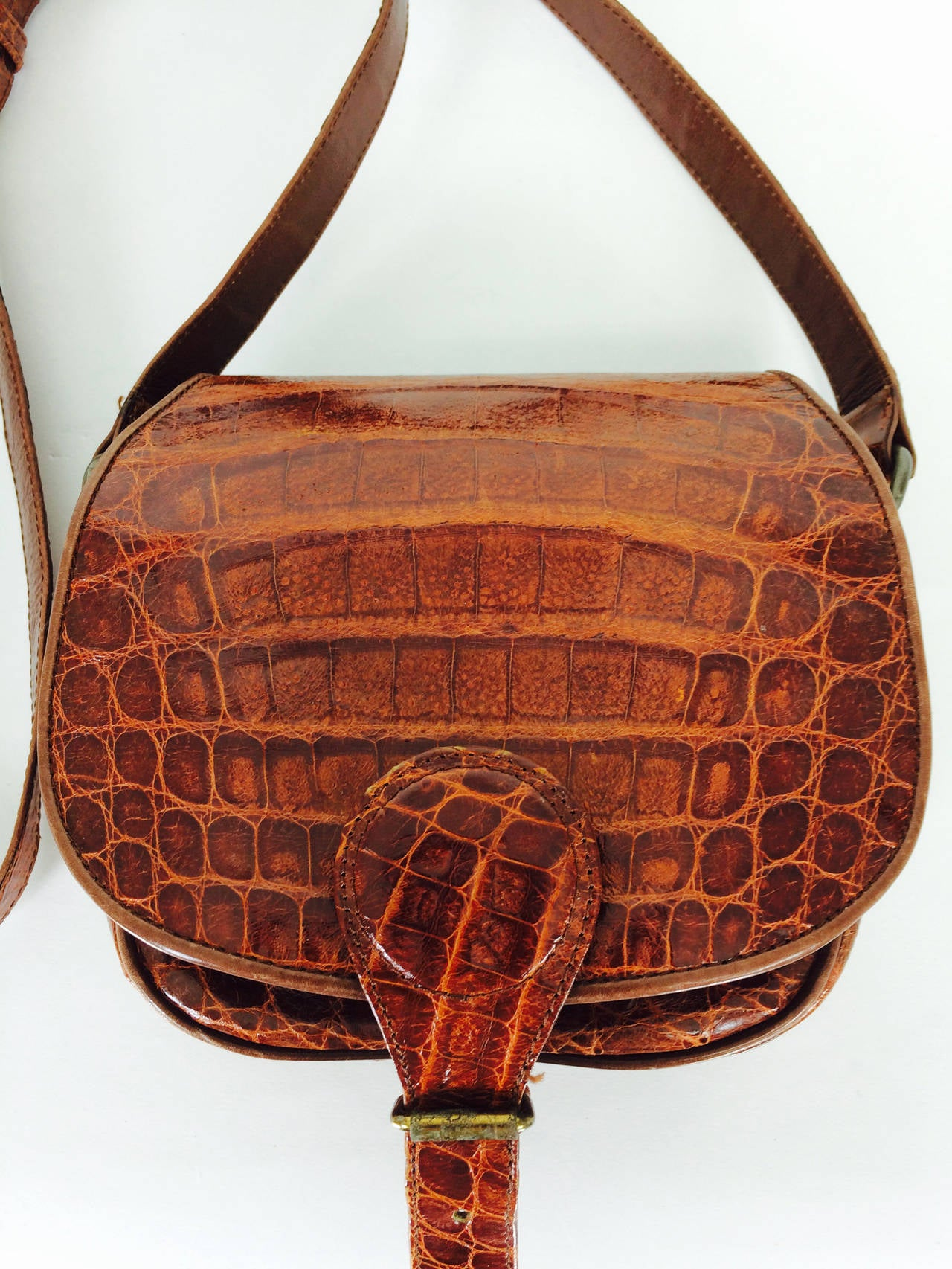 Saddle bag style handbag of cognac leather, faux alligatior from  Neiman Marcus 1980s...Real leather in a warm cognac shade made to look like alligator, the leather is textured & feels real...Flap bag closes with a buckle or hidden snap, your