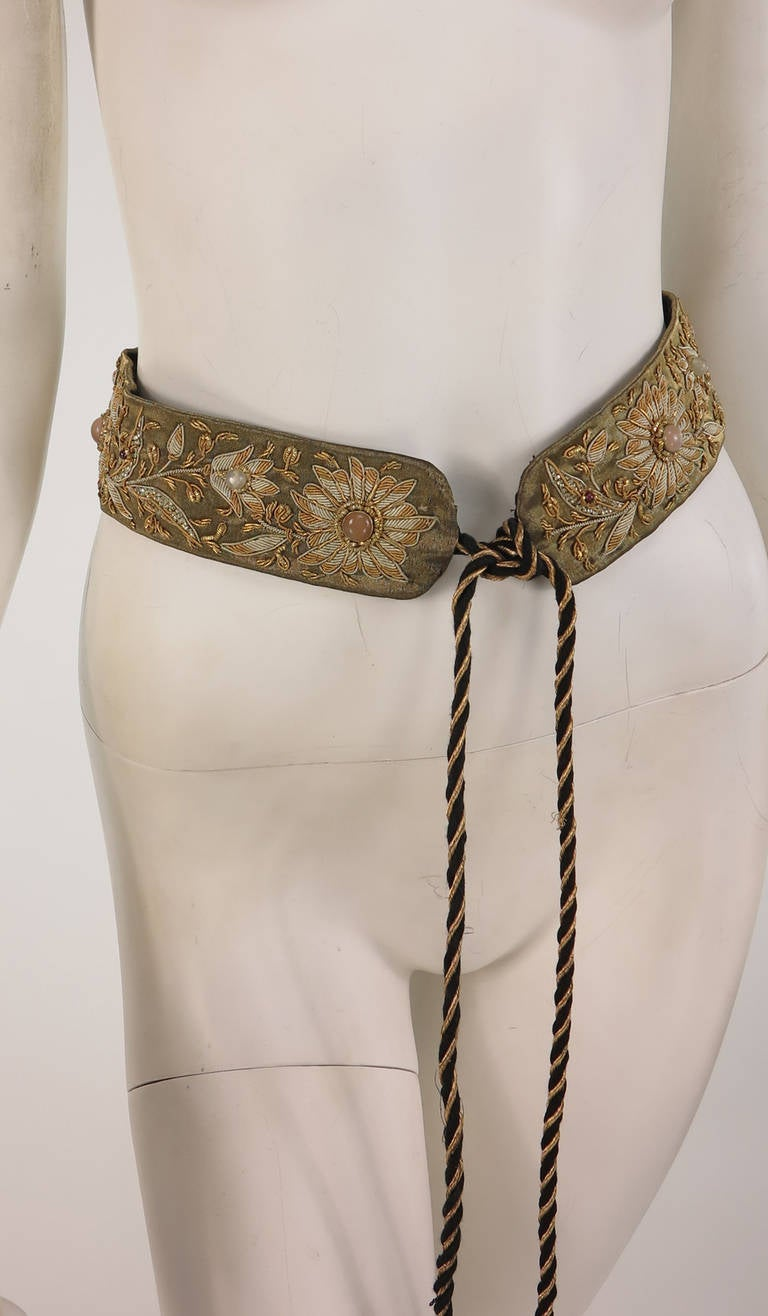 1960s India burnished metallic embroidered belt with bezel set semi precious stones, possibly moonstones...The wide belt is heavily embroidered in burnished gold thread in a foliate design, the flowers are set with oval cabochon stones...The belt