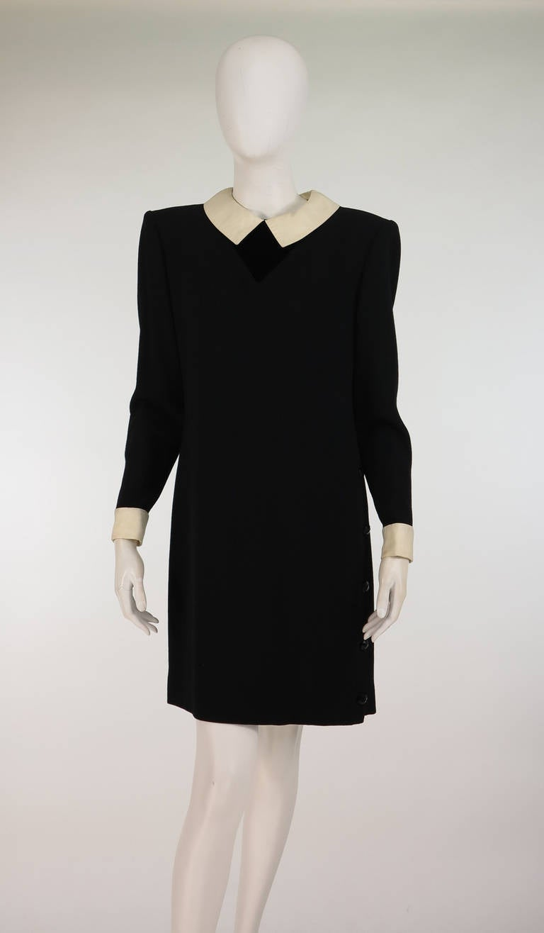 Valentino Studio, 1980s black wool crepe dress...Attached off white silk collar and cuffs add a Mod touch...Semi fitted, long sleeve dress has moderate shoulder padding,  side front button detail from the hip to the hem...Fully lined, closes at the