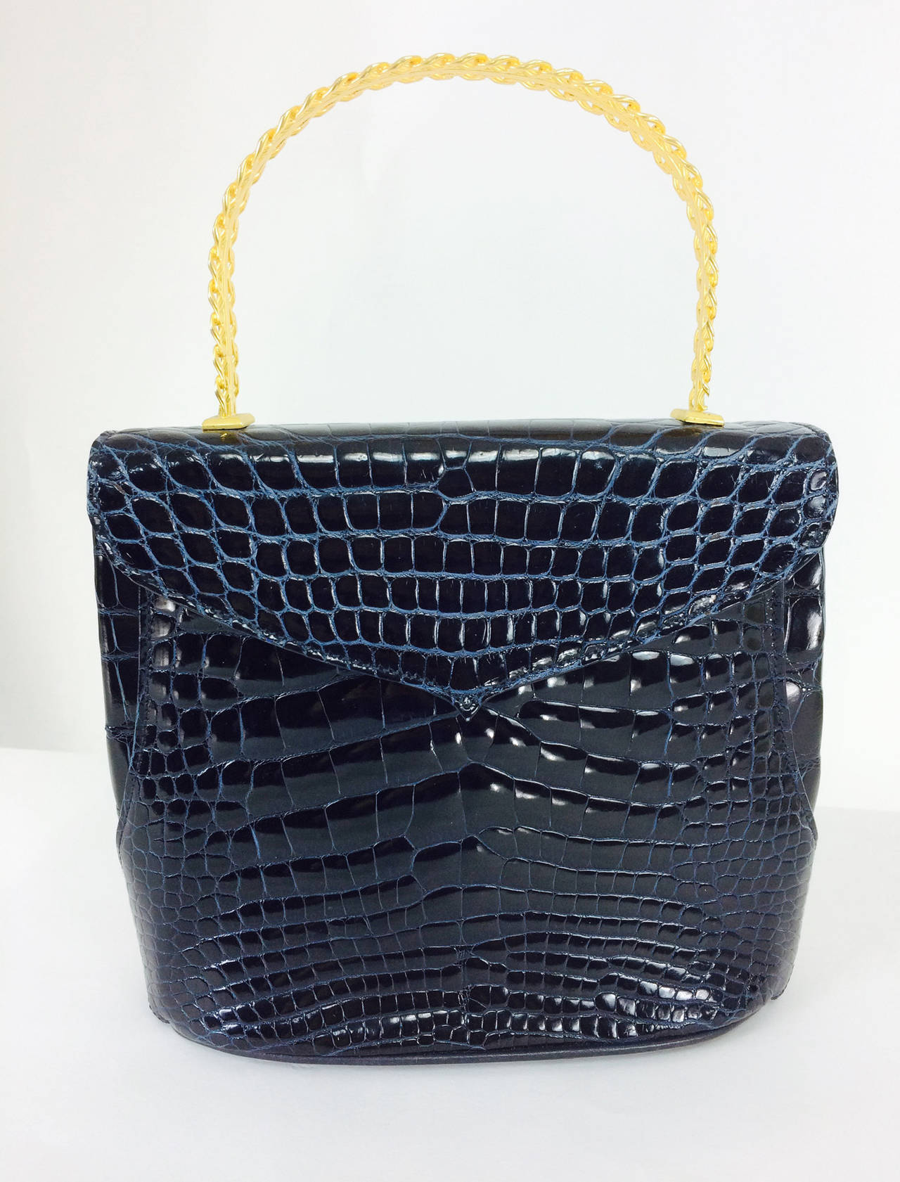 Lana Marks Lana of London navy blue glazed alligator handbag 1980s...Beautiful glazed alligator with a fixed gold woven handle that has a strip of alligator to match the bag...Lined in navy blue leather...The interior has a side zipper compartment