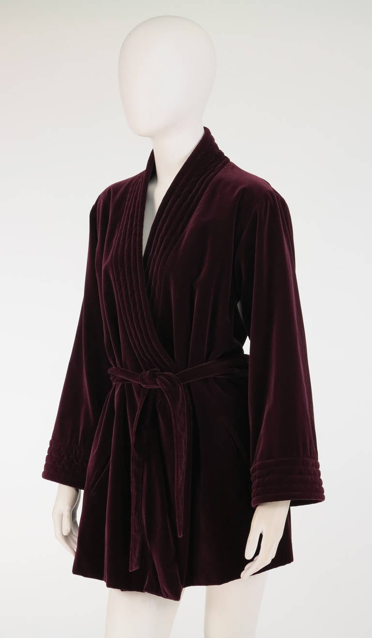 "Cut like a mens Victorian smoking jacket, this 1970s Yves St Laurent garnet velvet wrap jacket is stylish with a capital ""S""...Done in a soft cotton velveteen, it has a wrap front with facings that have top stitch detail, with ties inside and a self"