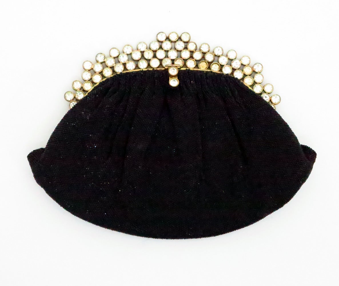 Fabulous Josef black caviar beaded evening bag with a rhinestone jewel frame...Lined in ivory satin, there are two inside compartments and the original mirror...Closes with a rhinestone jewel tab...Some light aging to the lining...One stone on the
