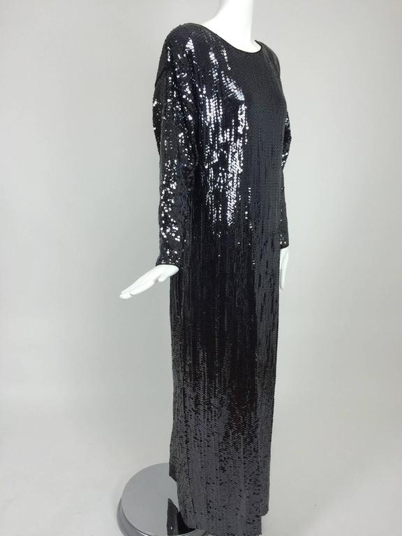 Halston glittery black sequin bat wing evening gown from the late 1970s...bateau neckline gown is trimmed with satin facings...long bat wing sleeves taper to the wrist...The dress has a deep center back vent for ease in walking...Covered in inky