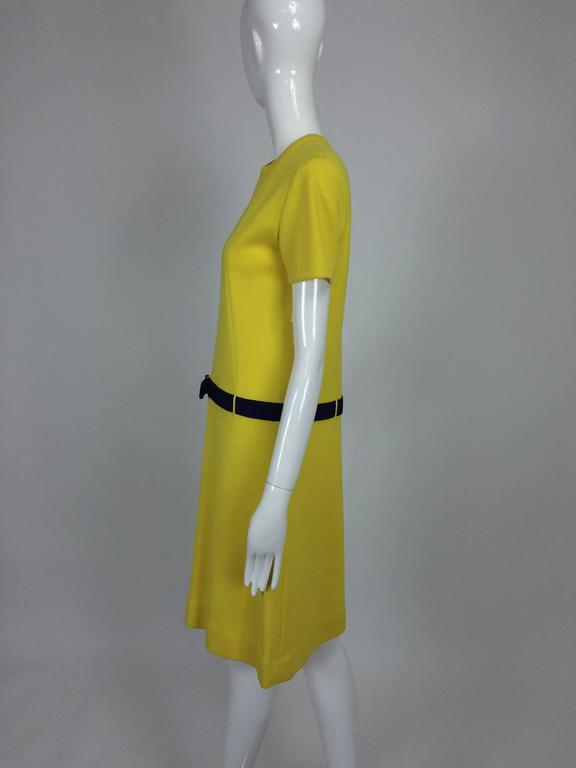 Mod style lemon yellow & purple double knit colour block mini dress from the early 1970s...A line dress has a jewel neckline and short sleeves...An attached purple knit waist band belt has a decorative bow at the front, self loops...The dress is