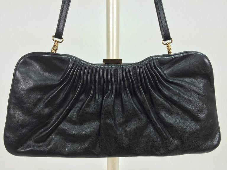 Escada black leather frame bag convertible clutch or shoulder handbag...Black leather frame bag has gold logo clasp and attachments for the removable strap...The bag is pleated at the top on both sides...Inside the bag is lined in brown fabric,