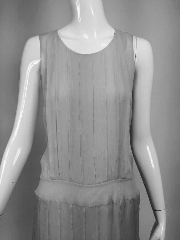 Chanel dove grey silk chiffon pleated afternoon dress 2006...Dove grey silk chiffon sleeveless dress with jewel neckline, pleated bodice, banded hip and open pleated skirt...Fully lined in silk chiffon...The dress closes at the back with snaps and a