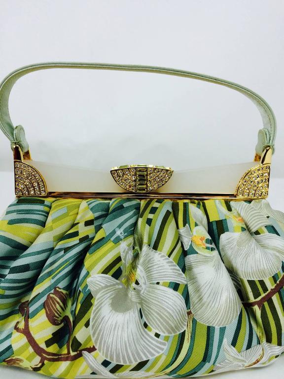 Judith Leiber plexiglass & jewel frame silk tropical orchid print handbag...Frosted white plexiglass handle with crystal jewel clasp and gold hardware frame handbag...Mint green silk handle, the bag is a tropical print with greenery and