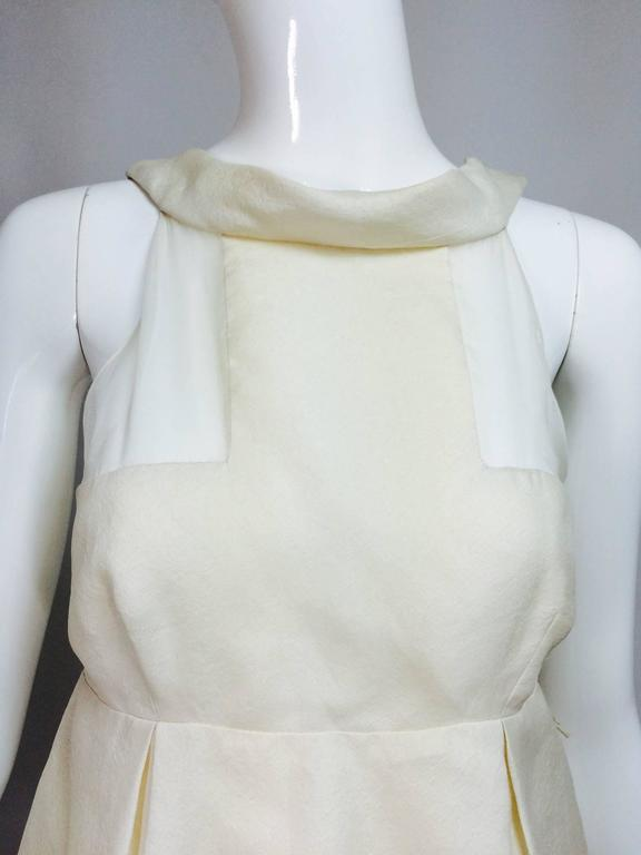 J Mendel ivory silk pearl hem sheer bodice mini dress. Sleeveless dress has a rolled band collar, the bodice front is pieced with transparent silk and woven silk, the back is sheer silk and gives the appearance of a backless dress. The skirt has
