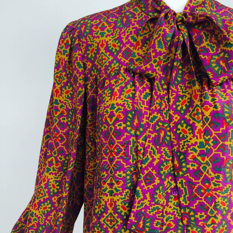 Yves Saint Laurent Moorish design silk print bow tie blouse...Long sleeve blouse, in a light weight crepe, shoulder yoke front and back, closes at the front with buttons and a bow tie neck...Long full sleeves have button cuffs...Marked size 36, fits