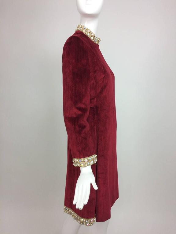 Garnet red silky cotton velvet, jewel trim Mod dress 1960s...Gold cord and jewels at the stand up neckline, cuffs and sides & back of the hem...The dress has a hidden zipper at the front and closes with hook and eyes at the neck front...Long sleeves