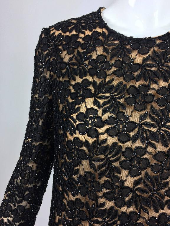 Mod style shift dress from the early 1960s...Black floral lace is beaded in black glass beads...Jewel neckline, long sleeves slightly A line dress...Lined in nude organza...The dress closes at the back with a zipper and hook and eye...Custom
