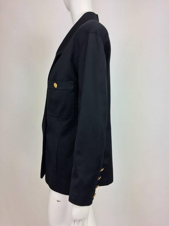 Chanel black silk military style pea coat/jacket...Double breasted with gold Chanel buttons...Patch breast pockets with gold Chanel buttons and vertical front seam hand warmer pockets at the lower front...Hip length with slight waist shaping...4