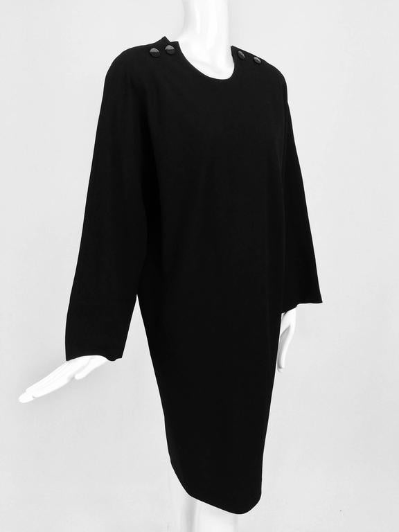 Vintage Jean Muir black wool crepe dolman sleeve dress 1980s...Pull on dress with padded shoulders, working buttons at each shoulder top...Dolman sleeves with wide cuffs that can be turned back...Sack style dress narrows to the