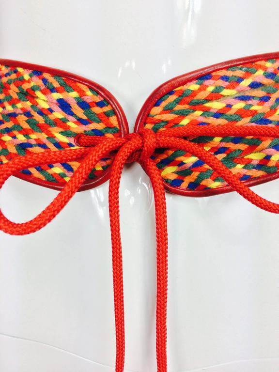 Vintage Yves Saint Laurent woven coloured cord and leather belt 1960s...Wide woven cord in red, orange, green and yellow trimmed with red leather...Closes at the front with long red cord ties each end has a red wooden bead...Marked size B