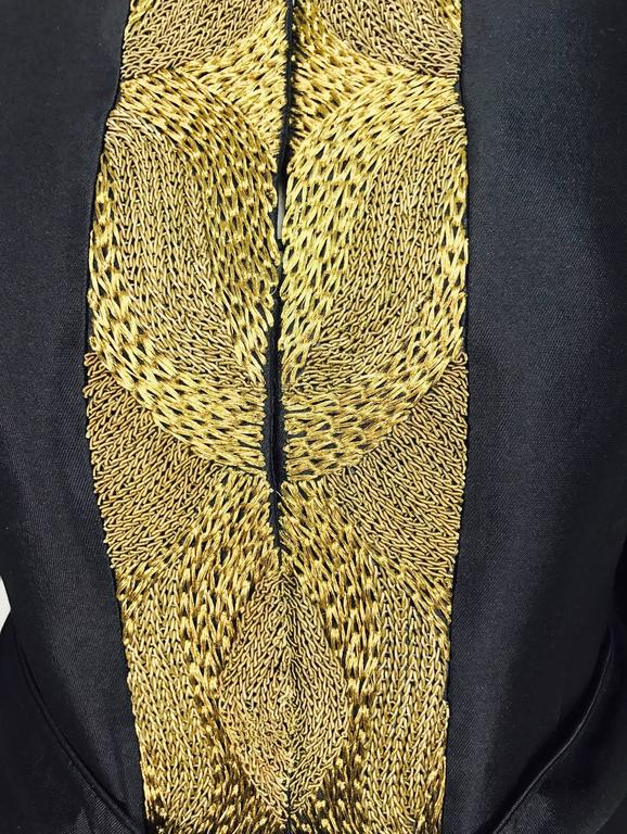 This amazing jacket from Rena Lange is black wool and silk, but feels like silk...Heavy gold cord embroidery is a real eyecatcher...Hidden button and loop closure at the front and each side facing is embroidered...Round neckline...Long sleeves with
