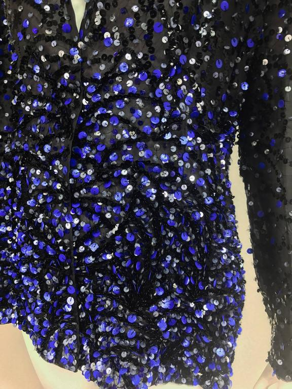 Glittery black and blue sequins embroidered on a black silk organza jacket...Long sleeves narrow band collar...Jacket is open at the front...Fully lined in silk organza...Shaped at the waist and fits over the hips...Unworn with tags...Marked size 10