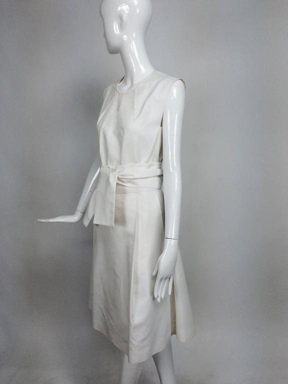 Yves Saint Laurent sleeveless white cotton and silk wrap waist dress...Jewel neckline, sleeveless dress...The bodice at the neckline has diagonal open pleats the fan towards the bust, the outer seams have raw edges...The skirt has open pleats at