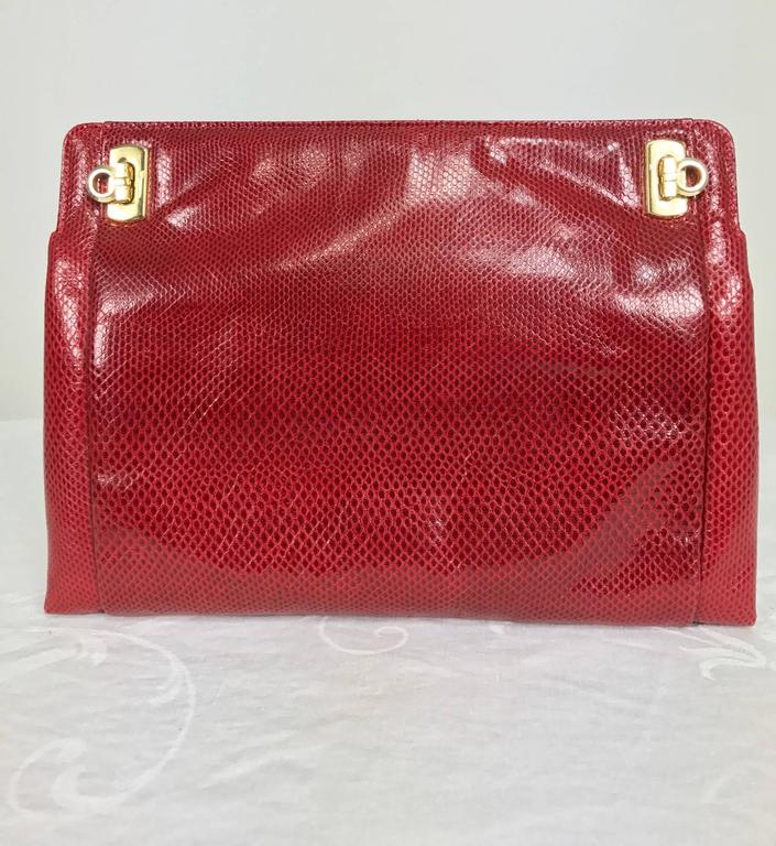 Vintage Ferragamo red lizard clutch cross body handbag 1980s...Cherry red lizard bag has gold hardware closes with 2 turn locks at the front top of bag...Long narrow shoulder strap has gold clasps to use or remove...Lined inside in black with a