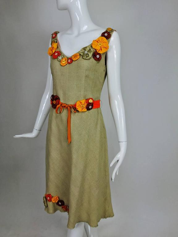 Moschino natural mid weight silk linen sleeveless shift dress with scoop neckline trimmed with brightly coloured fabric flowers with button centers...A line skirt has flower appliques at the skirt side front, the hem is a raw edge narrow
