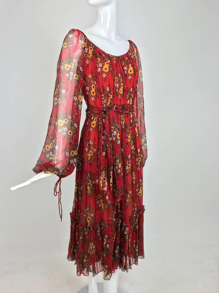 Bohemian style peasant dress from the 1970s, labeled House of Arts...Sheer silk in dark red with a floral print...Scoop neckline, raglan sleeves with tie cuffs...Full gathered skirt with a deep ruffle hemline...Together with the original self tie
