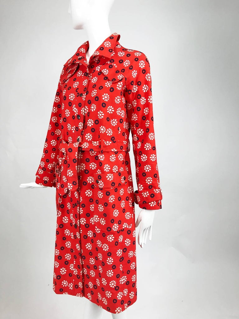 Fabulous Ungaro Parallele red, white and navy blue with black center circles with white floral printed red cotton canvas trench coat from the late 1960s...Black snap front coat has a self tie belt, shoulder flaps at the front, 2 hip front patch