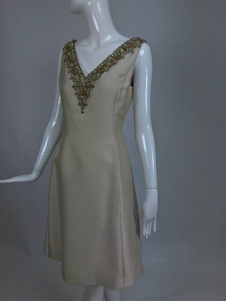 Vintage Malcolm Starr jeweled V neck lustrous cream silk dress from the early 1960s...Princess seam dress has a deep V neckline that is heavily beaded and has crystal set rhinestone trims...Beautiful lustrous mid weight silk dress has front on seam
