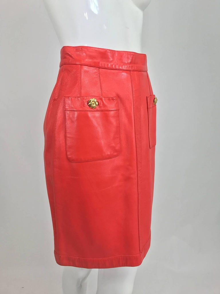 Chanel Vintage 1990s coral red leather skirt with pockets...Soft leather skirt sits at the natural waist, is fitted through the hip and falls straight to the hem...Two hip front patch pockets close with gold Chanel camellia flower buttons, lots of