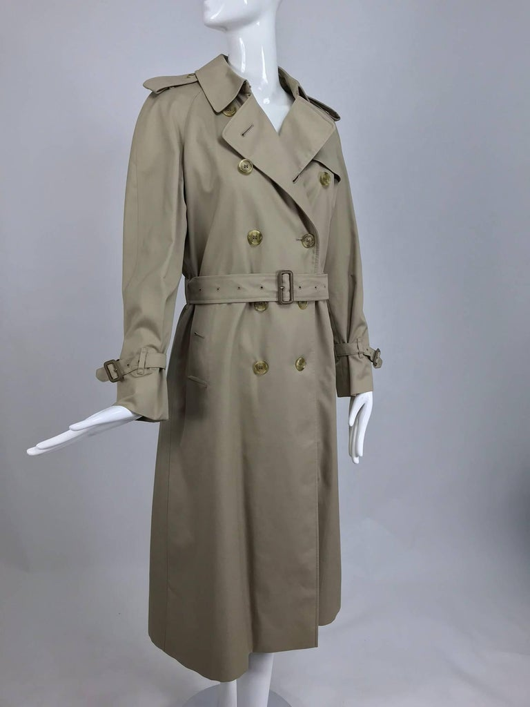 Burberrys classic tan poplin trench coat with zip out removable nova check wool lining...All the classic trench coat details are here, epaulets, storm flap, self belt, pocket flaps, raglan sleeves sleeve buckle bands, deep back vent with button