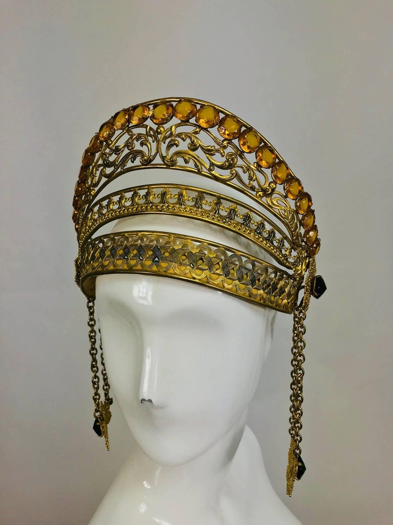 Rare Crown or headdress from the early 1900s, constructed of embossed, cut out and woven gilt metal, the top is set with amber cut faceted jewels...At each side are gold filigree disks set with faceted green stones, hung below are chains, the