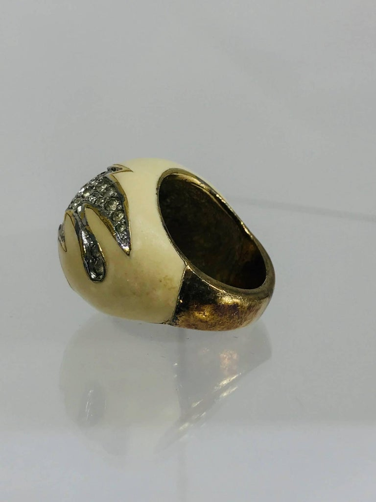 1970s cream enamel dome top vermeil ring set with rhinestones...Sterling silver ring has a gold wash, the dome top is cream enamel set with a modernist design edged in silver with crystal rhinestones. Fits a size 6