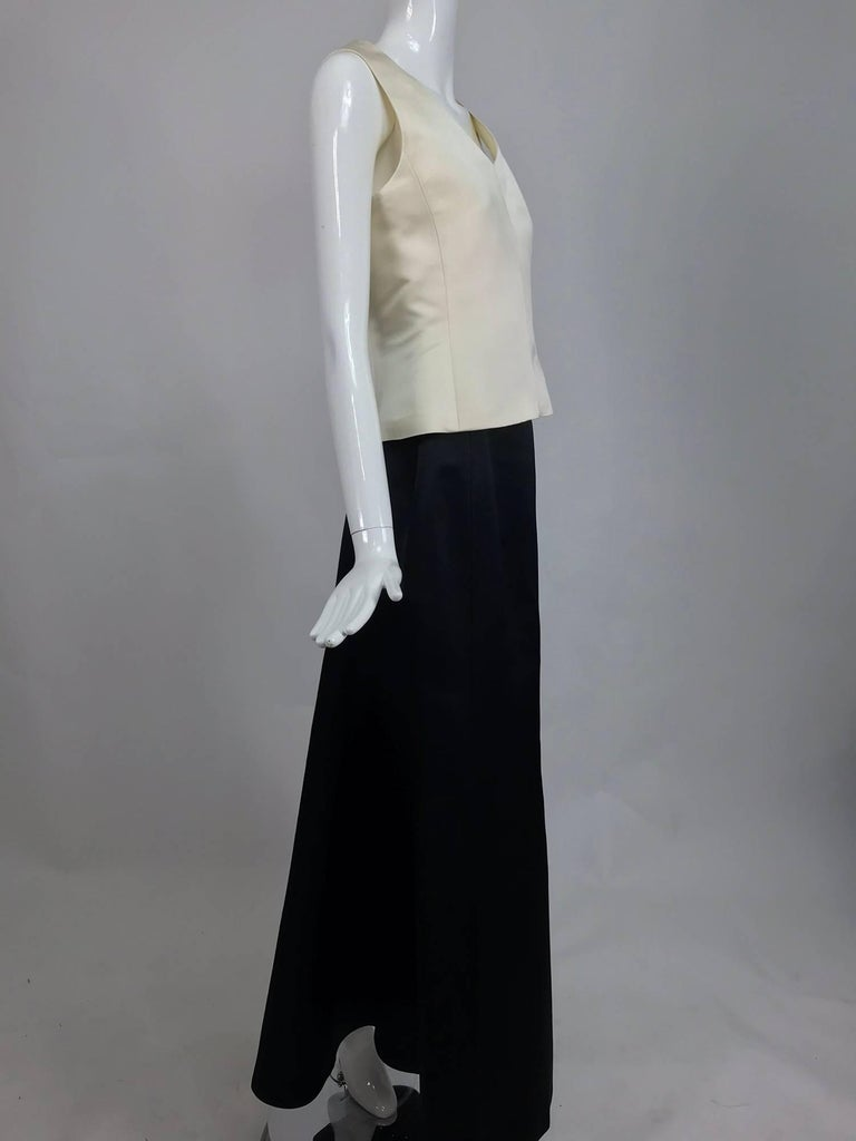 Vintage Bill Blass evening skirt set in cream and black silk satin from the 1980s. Sleeveless princess seamed v neck top is fitted through the waist and flares at the hip, it closes at the back with a zipper, fully lined in silk. The full length