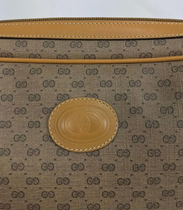 Vintage Gucci logo coated canvas and leather clutch 1980...Tan with dark brown Gucci logo print. This bag closes at the top with a zipper and Gucci leather tab. Open compartment inside, fully lined inside, lining has a couple of scratches but