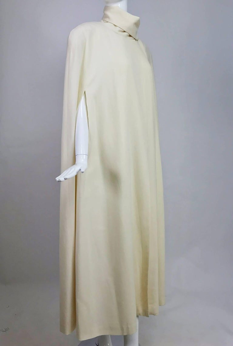 Winter white full length wool cape from the 1980s...Perfect for evening or daytime...Long A line shape cape closes with hidden snaps at the neck side front, there is an attached self scarf that can be wrapped around the neck or thrown over the