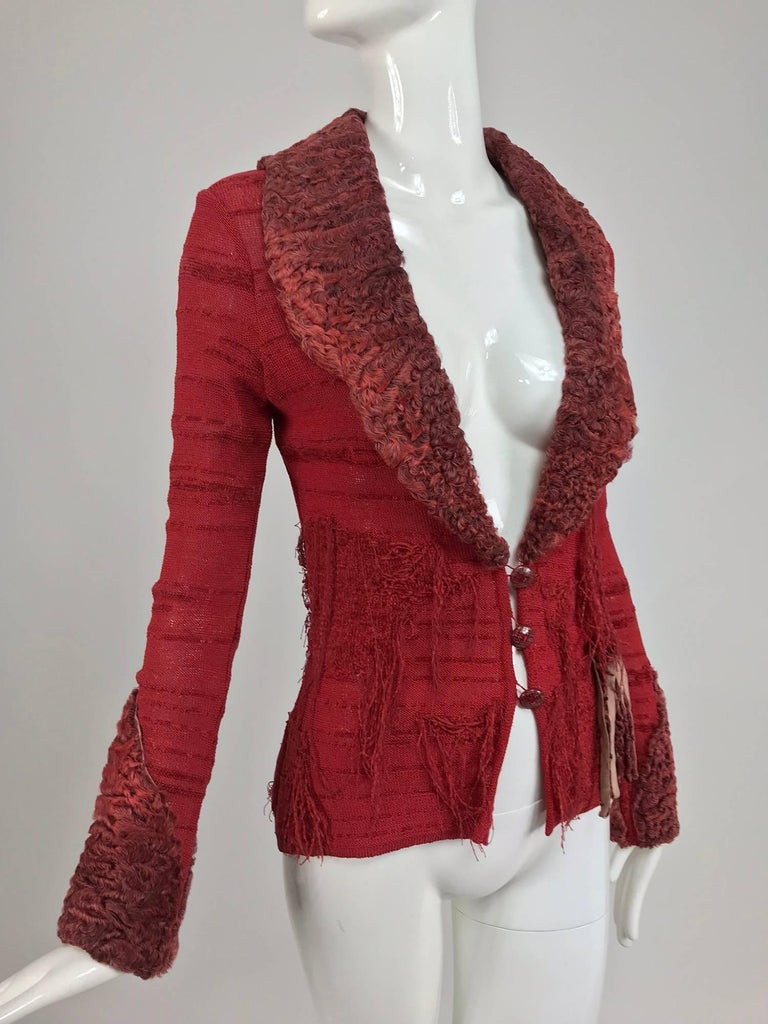 Christian LaCroix brick red sweater with dyed lamb fur trim...Cardigan sweater with dyed red lamb fur collar cuffs and appliqued fringe...This sweater is knitted in an irregular pattern using rayon and velvety synthetic yarns to create a unique