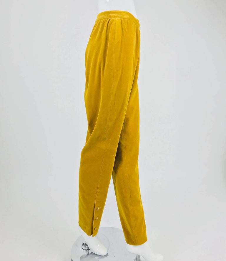 Chanel golden yellow velvet trousers with ankle buttons from the 1990s...Soft golden yellow velvet trousers sit at the natural waist with a waist band that closes at the side with button at the waist and a zipper below...Fuller at the hip and thigh