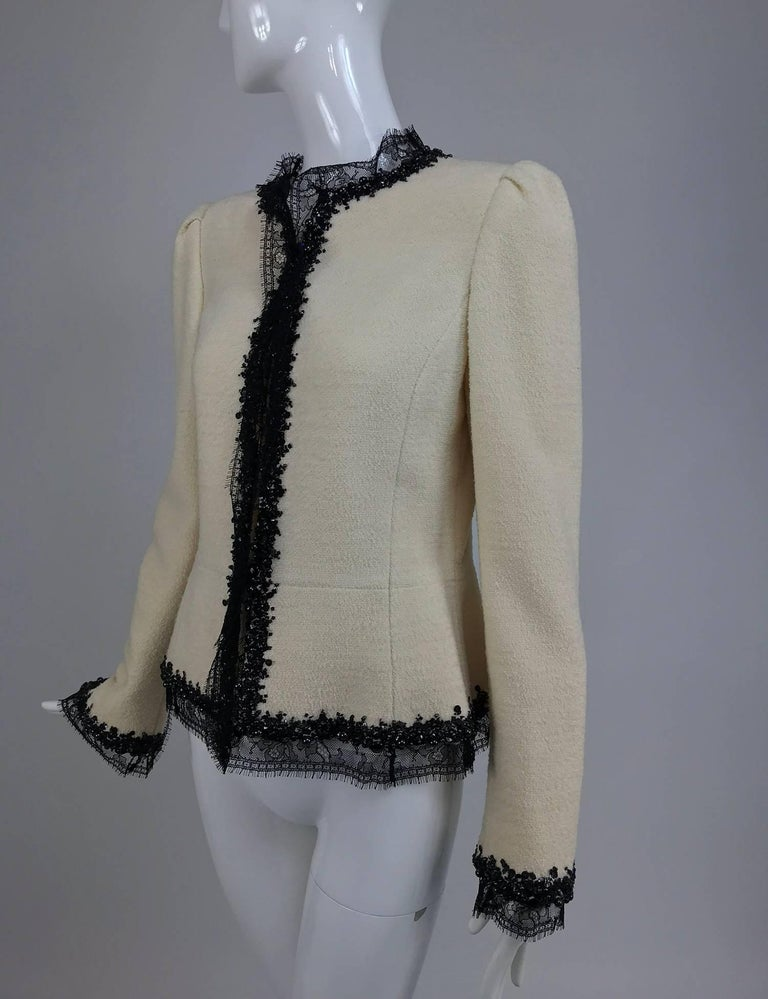 Oscar de la Renta winter white boucle jacket with black lace and beaded trim...This beautiful jacket has lace and beaded trim on the neck, front facings, hem and cuffs decoration extends to the elbow from the wrist...The jacket has a peplum