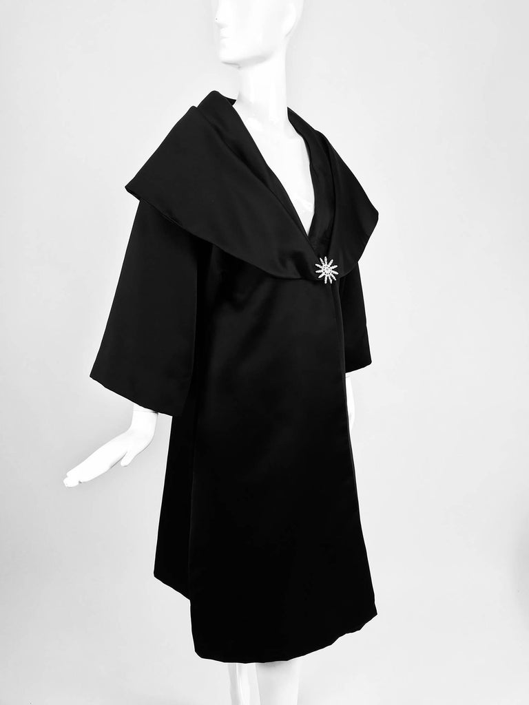 Carol Mignon Boutique Black portrait collar jewel closure evening coat from the 1980s...A beautiful coat that looks unworn...Portrait collar,crystal rhinestone jewel at the front closure...Bracelet length raglan sleeves... In excellent wearable