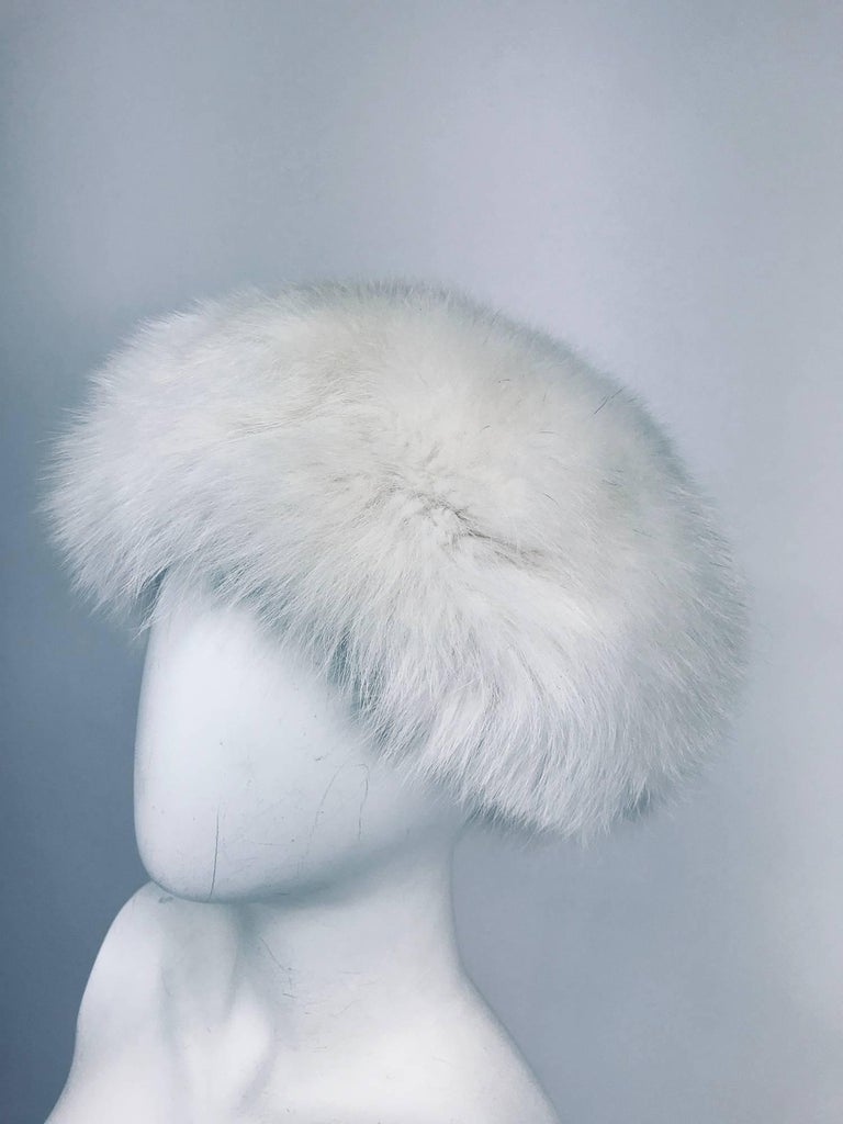 White fox hat from the 1960s...A beautiful full and fluffy hat in a creamy white but not yellow at all...Lined in black...Fits size small-medium...It is in excellent wearable condition with no issues... Inside band is 25