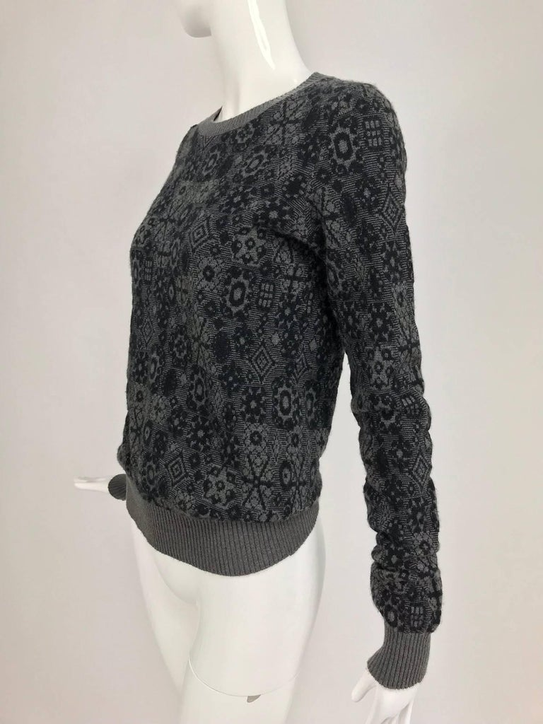 Chanel grey cashmere pull on sweater with a modern snowflake pattern...Pull on sweater has ribbed collar, cuffs and hem...Marked size 38... In excellent wearable condition... All our clothing is dry cleaned and inspected for condition and is ready