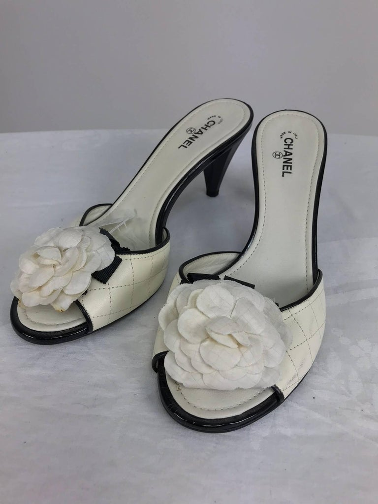 Chanel cream quilted mules with patent heels and Camellia flowers at the front 38 1/2 M...The left shoe outside near sole has some very light scuff marks, see photo, there is a bit of yellow on the right lower flower petal see photo which looks