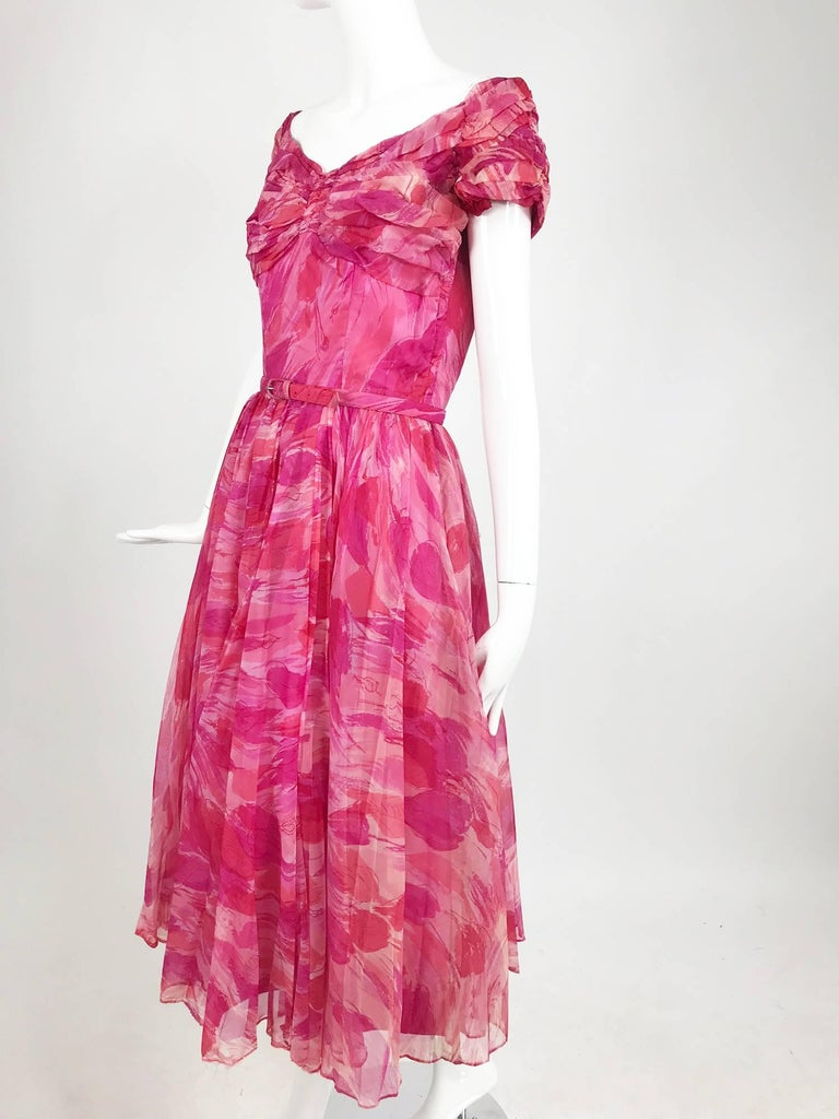 Hot pink modernist floral print off the shoulder, early 1960s organza dress. The bodice features raglan sleeves that sit at the shoulder edge, center bust front is gathered the bust is loosely pleated at each side, the bodice is fitted below to the
