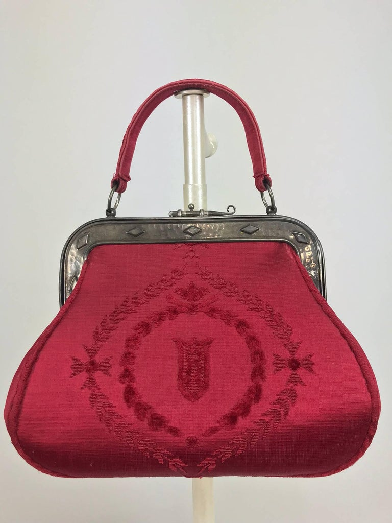 Roberta di Camerino red silk cut velvet metal frame handbag. Vintage bag has a burnished silver metal frame with a pull latch closure. The bag is a nice size and is in very good condition. Lined in red leather, there is a zipper compartment and two
