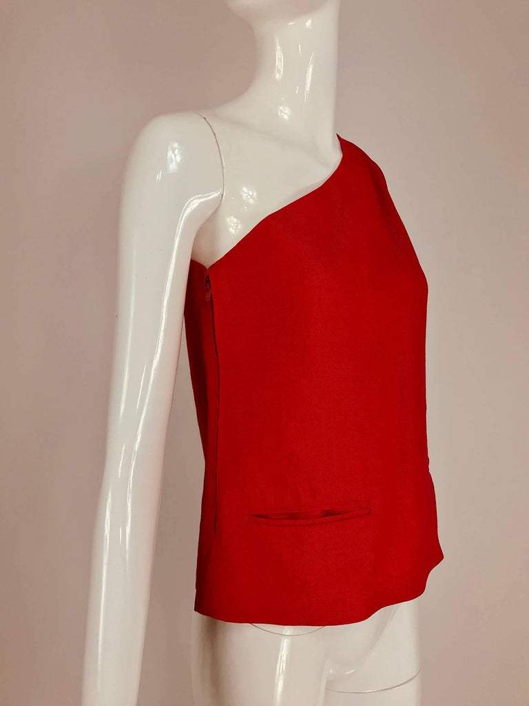 Bill Blass red linen one shoulder top from the 1970s. Bright coral red top has two besom pockets at the hip fronts. Mid weight linen. Closes at the side with a zipper and hook and eye. Looks great with white trousers. Fits a size small. In excellent