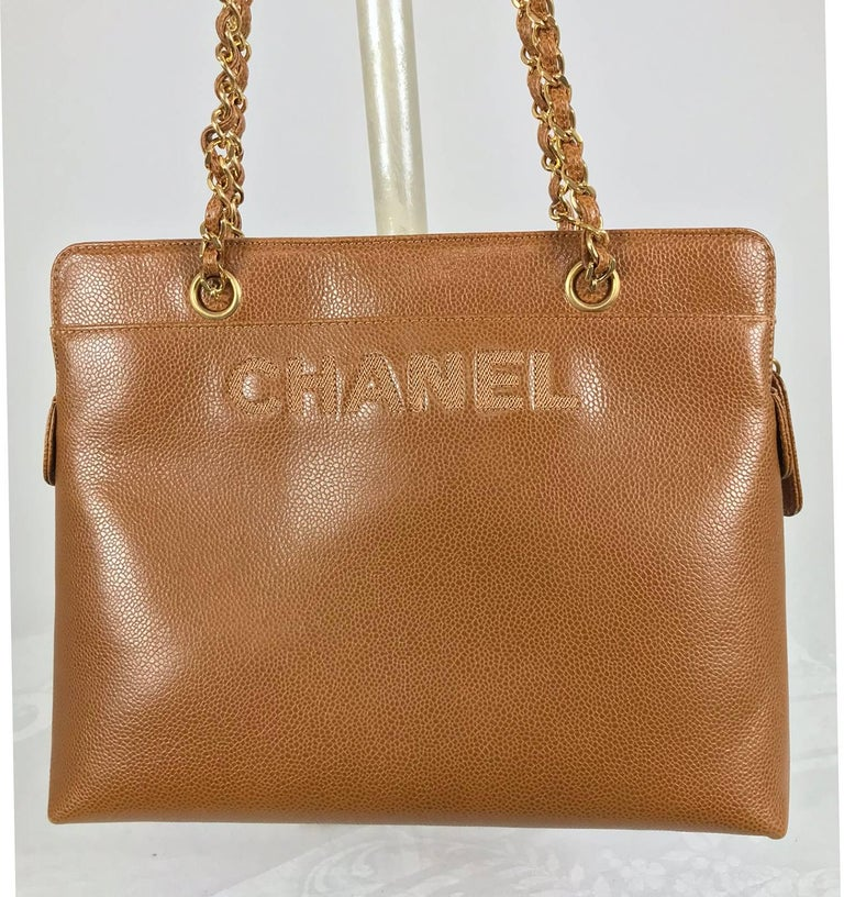 Chanel caramel pebble leather chain strap shoulder bag from the 1990s, never used. This beautiful bag is a rich caramel colour the leather has a light pebble texture. Chanel is embroidered in large letters at the upper front of the bag, there is an