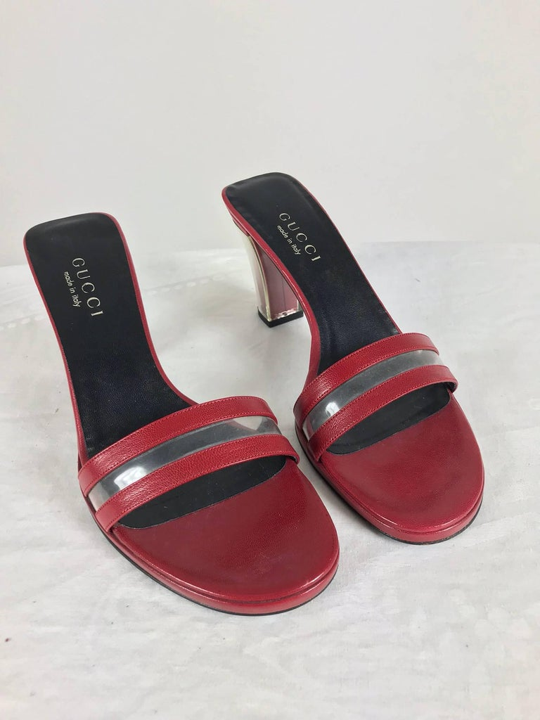 Gucci wine red leather Lucite heel mules 9B. Unworn. Beautiful shoes with high heel that is in-cased in Lucite. The front of the shoe is composed of two strips of leather with an insert of clear plastic. Foot bed is lined in leather.