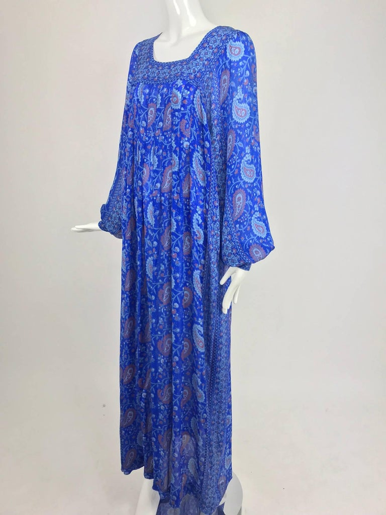 Raksha of Hindip London ink blue silk paisley print bohemian dress from the 1970s never worn. Tissue silk dress in a beautiful shade of blue with paisley print in brick red and pale blue. The neckline features a band yoke that dips low in the back,