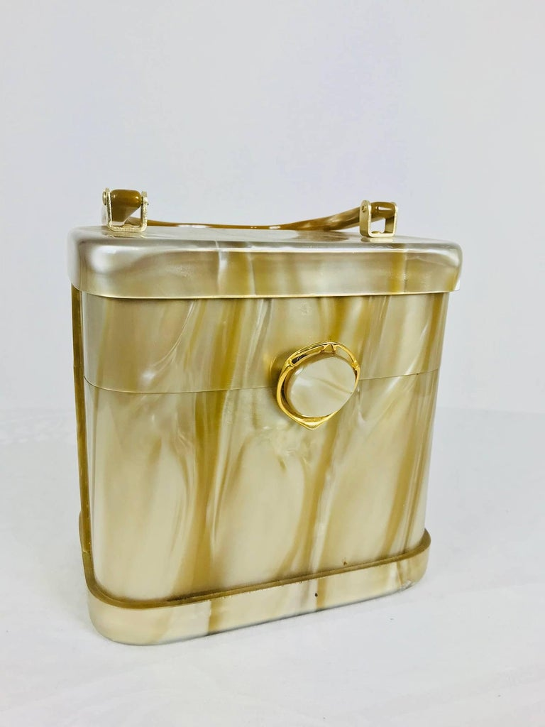 Stylecraft Miami gold pearlized Lucite handbag from the 1960s. Unique box shape handbag in a pale pearlized  cafe au lait colour. Box shape with gold hardware, it closes with a button snap at the front. Narrow handle. The interior is lined in tan